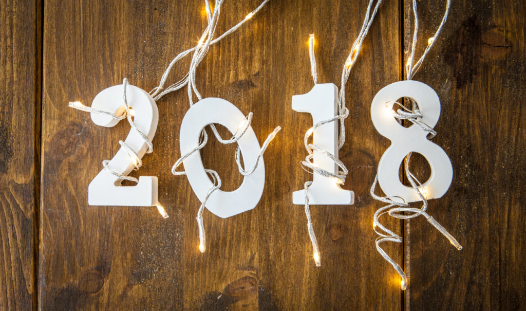 """""""2018"""" wooden pieces with mini white lights woven around."""